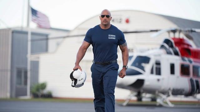 Dwayne Johnson mit Sonnenbrille im Pilotenanzug und mit Helm in der Hand.