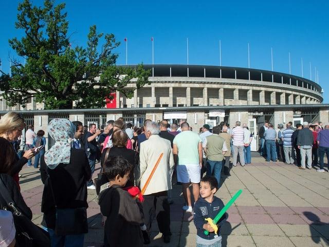 Menschen stehen in einer Reihe vor dem Olympiastadion