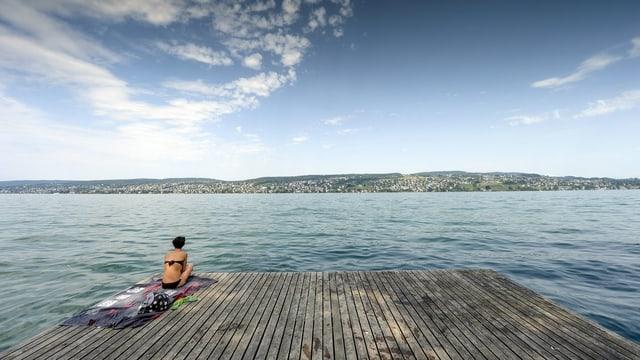 Eine Frau sitzt auf einem alten Holzfloss und blickt auf den blauen Zürichsee. Der Himmel ist mit leichten Wolken behangen.
