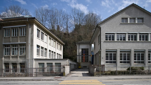 Zwei Gebäude und eine kleine Brücke. Es ist das Firmengelände der Revue Thommen in Waldenburg.