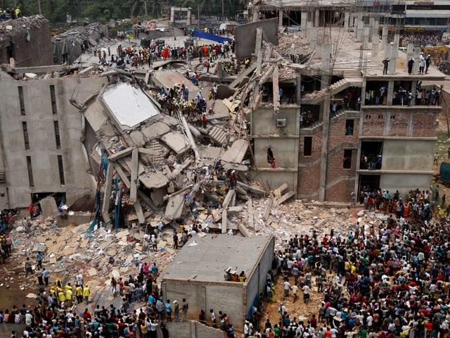 Panoramablück über das eingestürzte Gebäude und einer Menschenansammlung vor dem Trümmerberg.