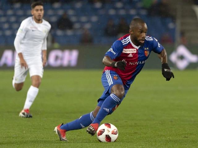 Ein schwarzer Fussballer am Ball, gefolgt von einem weiss gekleideten Gegenspieler.