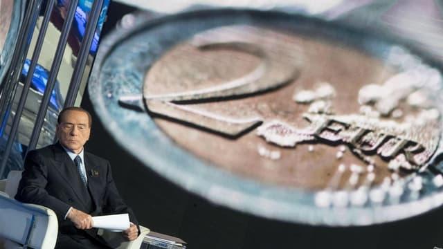 Berlusconi davant in grond maletg cun ina munaida da 2 Euros.