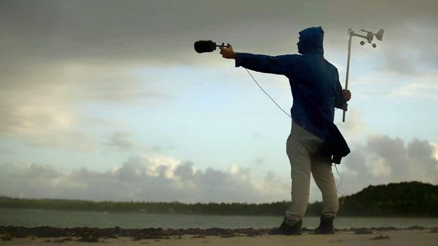Ein Mann steht am Strand und hält ein Mikrofon richtung Meer.