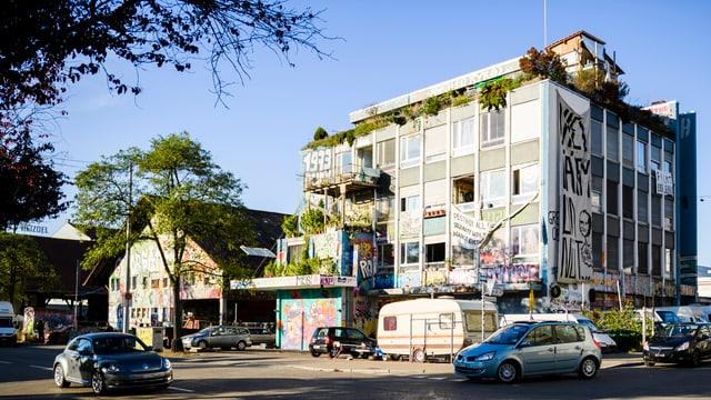 Ein Haus mit viel Graffiti dran. Davor steht ein Wohnwagen.