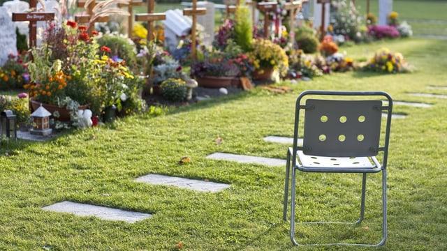 Ein leerer Stuhl steht vor frischen Gräbern.