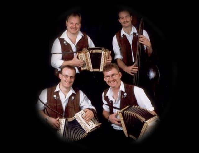 Drei Schwyzerörgeler und ein Kontrabassist auf einer Fotocollage mit schwarzem Hintergrund.