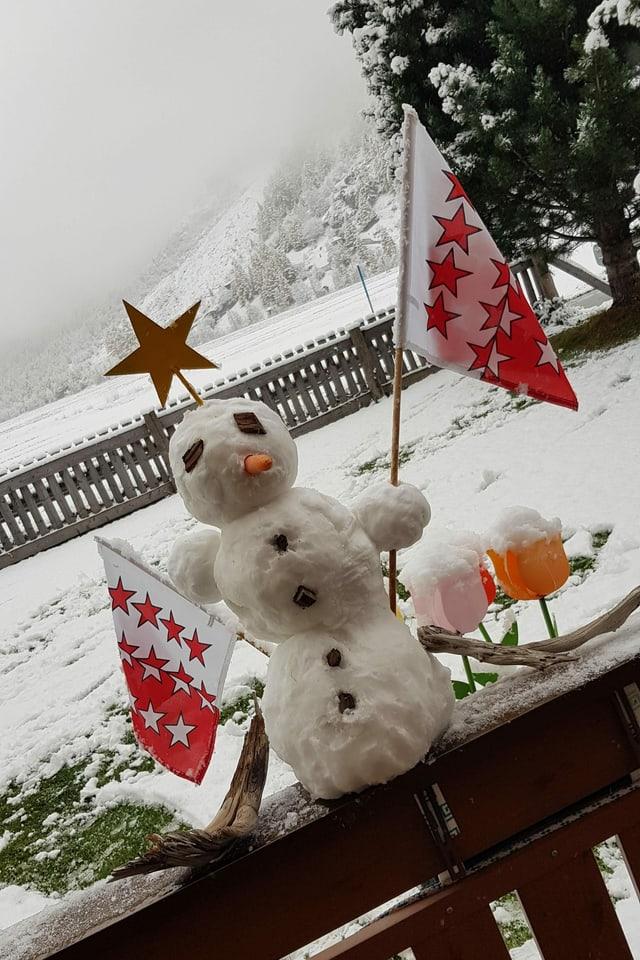 Kleiner Schneemann mit Wallis-Fahne auf dem Balkongeländer.