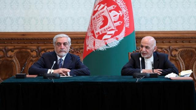 Abdullah und Ghani an einem Tisch vor einer Afghanistan-Flagge.