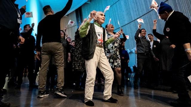 Leute tanzen und schwenken Grönland-Fähnchen.