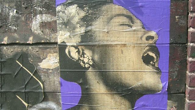 Plakat auf einer Mauer. Es zeigt Billie Holiday, wie sie mit expressivem Gesichtsausdruck singt.