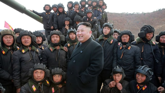 Nordkoreas Machthaber Kim Jong Un mit Soldaten, im Hintergrund ein Geschütz