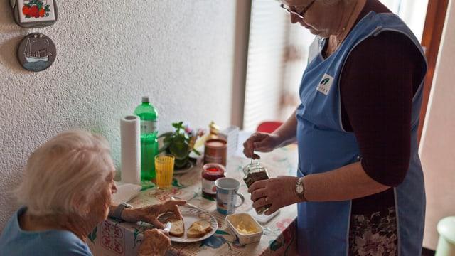 Spitexmitarbeiterin serviert alter Frau das Frühstück.