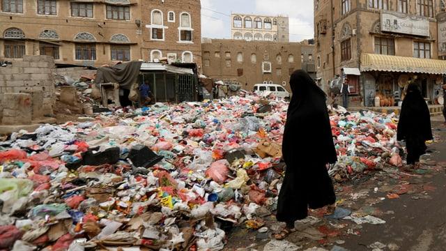 Haufen von Müll in der Stadt, einige Passantinnen.