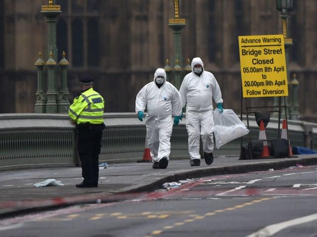 Zwei weiss gekleidete Forensiker gehen über die abgesperrte Brücke. Hinter ihnen das gelbe Warnplakat.