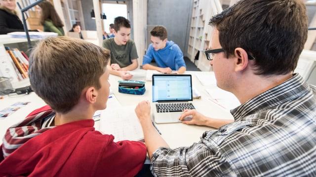 Ein Lehrer sitzt zusammen mit einem Mittelstufenschüler vor einem Laptop.