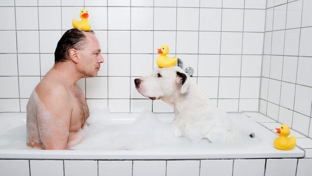 Ein Mann und ein Hund sitzen in einer Badewanne. auf dem Kopf tragen beide eine gelbe Quitschente.