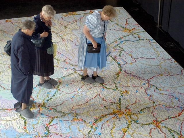 Drei ältere Frauen stehen auf einer grossen Schweizer Landkarte.