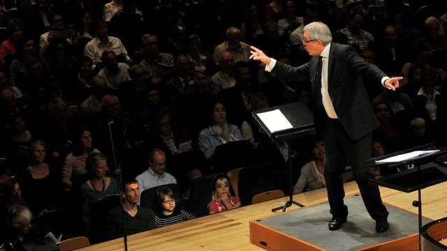 Ein dirigent vor der Publikum im Konzersaal des KKL