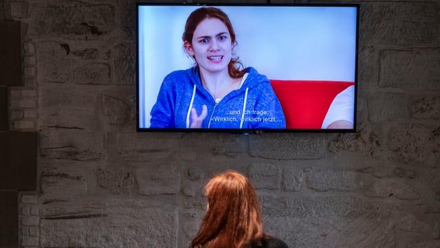 Eine Frau sitzt vor einem Bildschirm, auf dem eine andere Frau zu sehen ist.