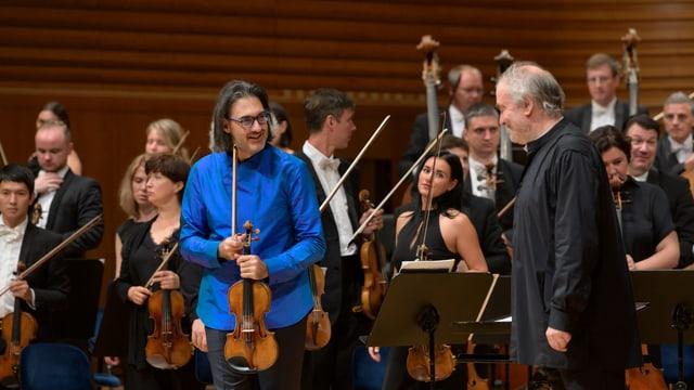 Geiger und Dirigent vor Orchester