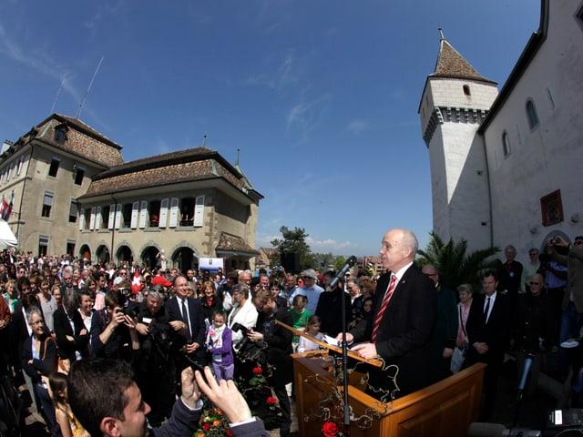 Maurer in Nyon auf einem Rednerpult, dutzende Menschen verfolgen den Auftritt mit.