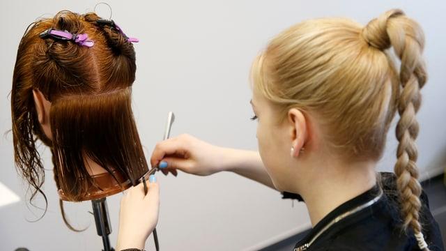 junge Frau mit blondem Zopf von hinten zu sehen, wie sie einer Puppe die Haare schneidet