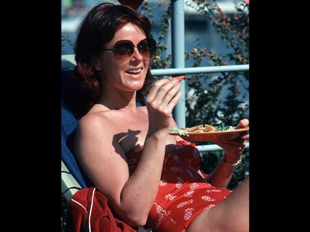 Anni-Frid geniesst eine Zwischenmahlzeit am Pool