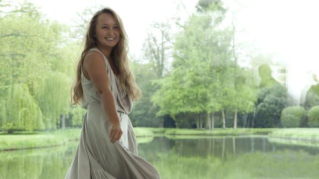 Julia Lezhneva in einem weissen Kleid lächelnd vor einem Fenster. Im Hintergrund ein Weiher und Bäume.