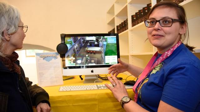 Patricia Pollinger erklärt einer Frau, wie ein Game funktioniert.