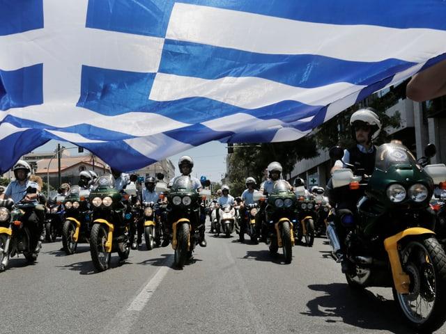 Polizisten auf Motorrädern unter einen Griechenland-Flagge