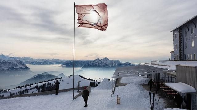 Schweizer Fahne im Wind beim Berghotel Rigi-Kulm mit Blick auf den Pilatus.