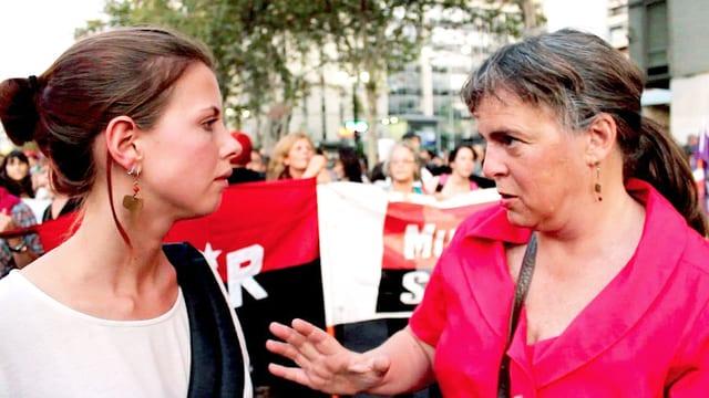Eine Journalistin hört einer Frau zu, im Hintergrund ein Demonstrationszug.