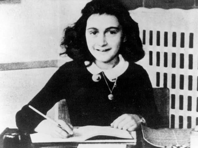 Anne Frank sitzt an ihrem Schreibtisch.