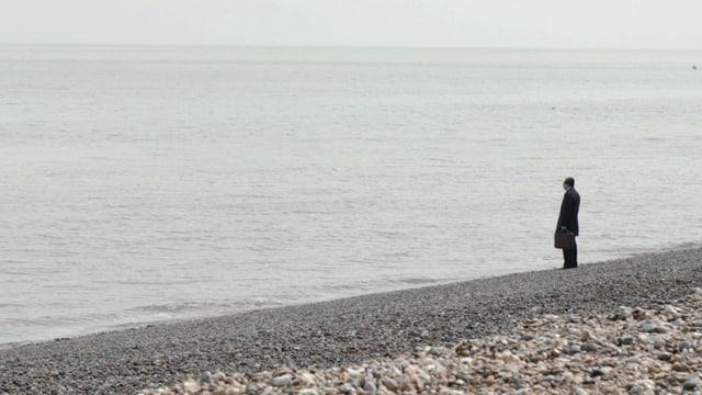 Ein Mann steht an einem Kieselstrand und blickt ins graue Meer hinaus.