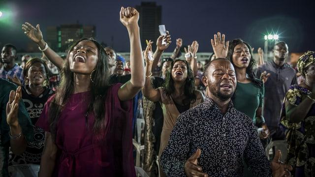 Anhänger einer Pfingstgemeinde halten ihre Hände in die Höhe.