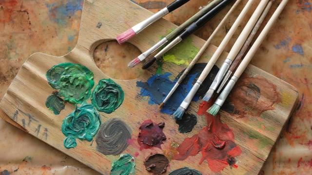 Eine Farbpalette mit Pinseln.