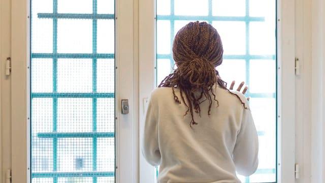 Eine Frau schaut aus dem Fenster. Sie ist in der Ausschaffungshaft.