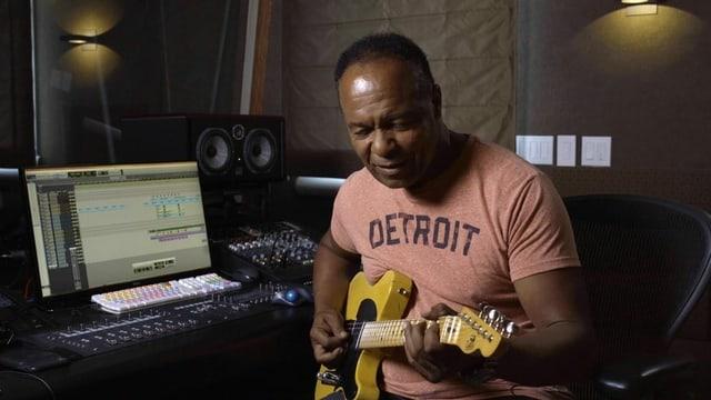 Ein schwarzer Musiker mit Gitarre im Studio.