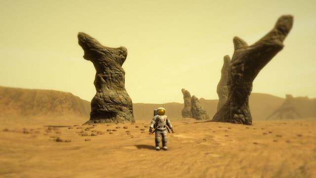 Der Astronaut steht in der Wüste vor einer Felsformation, die an tote Bäume erinnert.