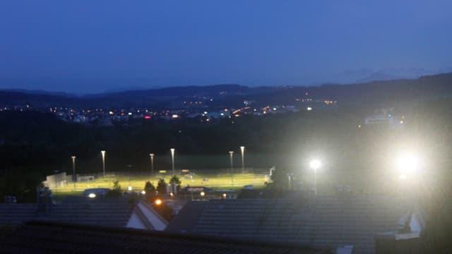 Ein Sportplatz bei Dunkelheit: links gut ausgeleuchtet aber blendfrei – rechts den Betrachter stark blendend.