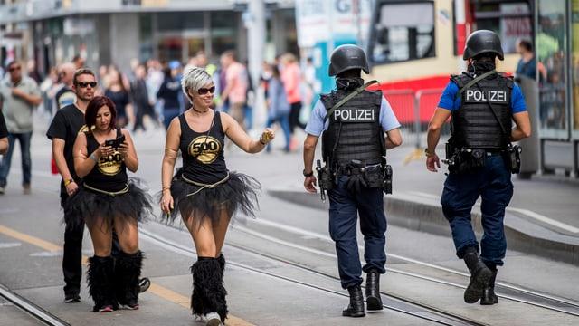 Zwei Frauen grüssen zwei Polizisten.