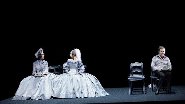 Zwei Damen in Kleidern udn ein Mann auf der Bühne