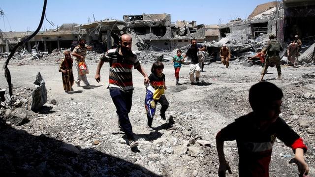 Zivilisten rennen durch eine zerbombte Stadt.