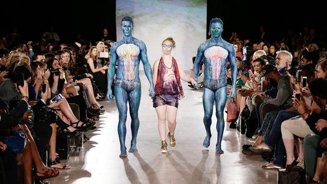 Auf dem Laufsteig zwei männliche Models, in ihrer Mitte ein Model mit Down-Syndrom.