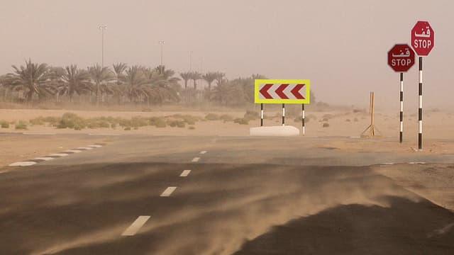 Eine Strasse in der Wüste, Sand wird vom starken Wind umhergeweht.