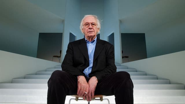 Werner Düggelin sitzt auf einem Stuhl, der mitten auf einer Theaterbühne mit abstrakter Architektur steht. In seiner rechten Hand hält er eine Zigarette.