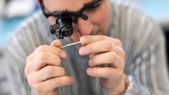 Ein Mann schaut durch eine Mikroskopbrille ein Stäbchen genau an.