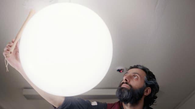 Ein Mann mit Bart wischt eine grosse, runde Deckenlampe mit einem Staubwedel.