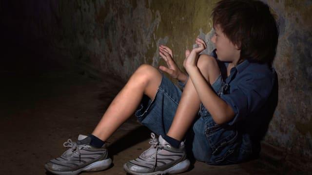 Ein Kind sitzt in einem dunklen Raum